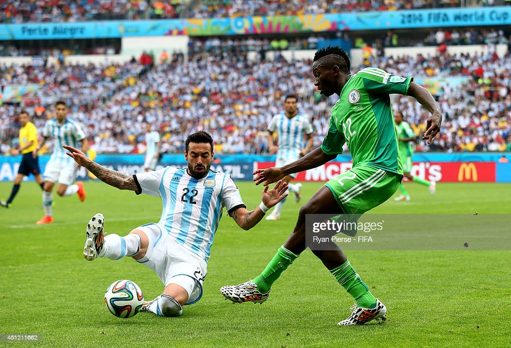 <a gi-track='captionPersonalityLinkClicked' href=/galleries/search?phrase=Kenneth+Omeruo&family=editorial&specificpeople=6392838 ng-click='$event.stopPropagation()'>Kenneth Omeruo</a> of Nigeria and <a gi-track='captionPersonalityLinkClicked' href=/galleries/search?phrase=Ezequiel+Lavezzi&family=editorial&specificpeople=5451126 ng-click='$event.stopPropagation()'>Ezequiel Lavezzi</a> of Argentina compete for the ball during the 2014 FIFA World Cup Brazil Group F match between Nigeria and Argentina at Estadio Beira-Rio on June 25, 2014 in Porto Alegre, Brazil.