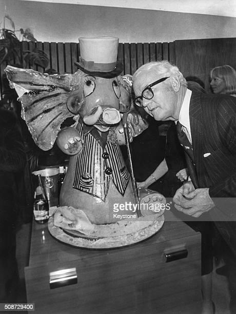 Kenneth Rush US Ambassador to France posing with an elephant made of sugar Paris circa 1975