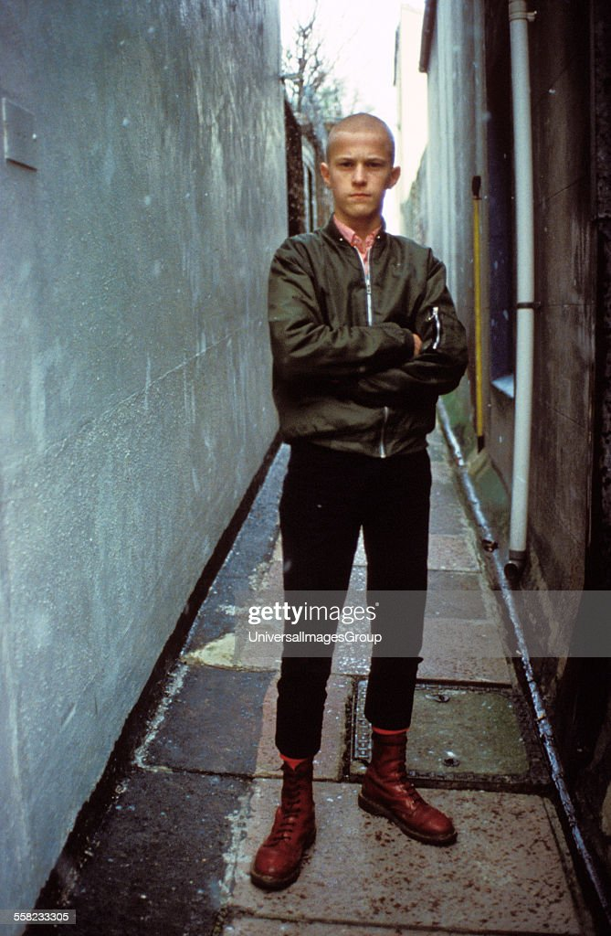 Kenny a young skinhead standing in an alley way wearing cherry red Dr Marten boots Brighton UK 12th Feb 1983