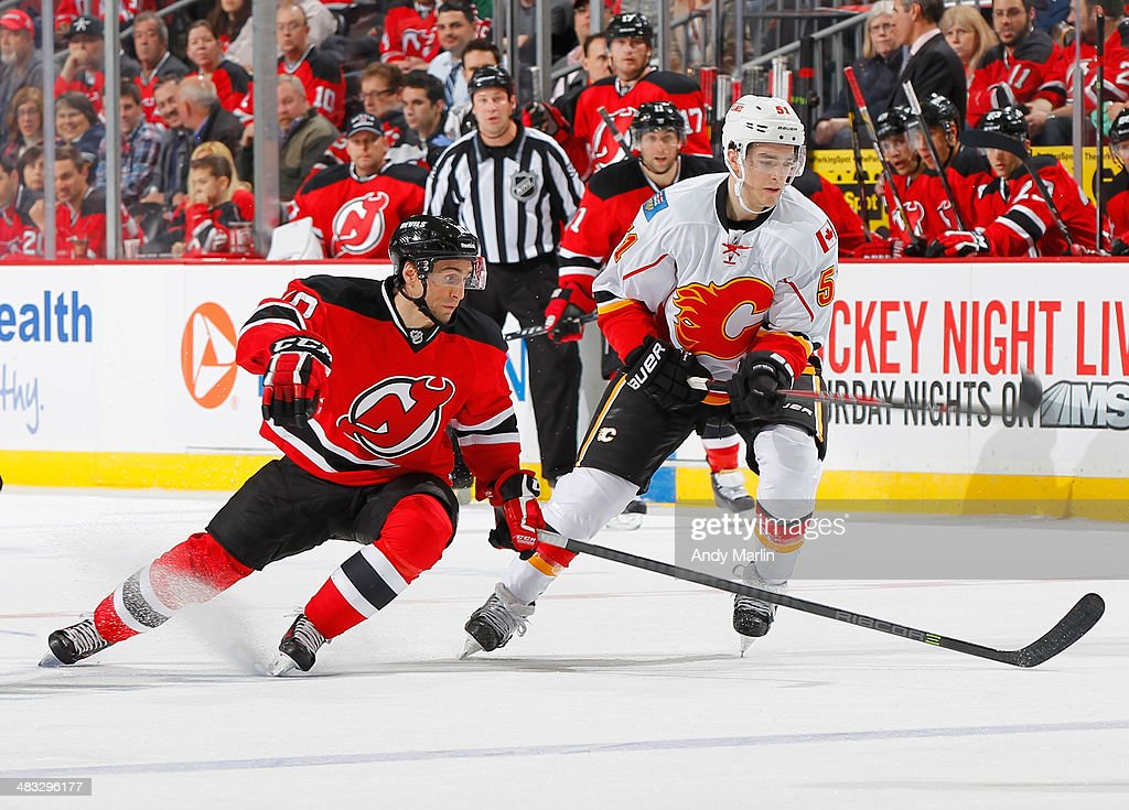 Kenny Agostino of the Calgary Flames skates against Peter Harrold of the New Jersey Devils during the game at the Prudential Center on April 7 2014...