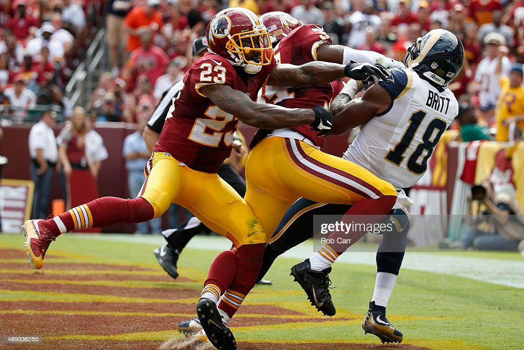 Kenny Britt of the St Louis Rams catches a touchdown pass while being defended by DeAngelo Hall and Trenton Robinson of the Washington Redskins...