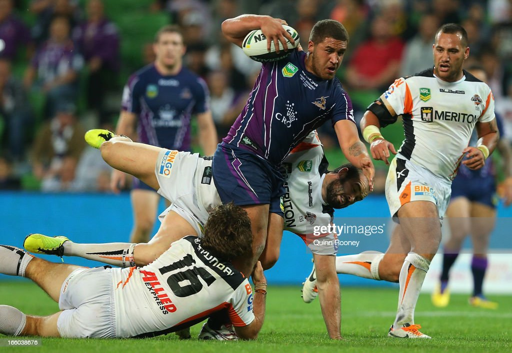 Kenny Bromwich of the Storm is tackled by Matt Bell and Aaron Woods of the Tigers during the round 5 NRL match between the Melbourne Storm and the Wests Tigers at AAMI Stadium on April 8, 2013 in Adelaide, Australia.