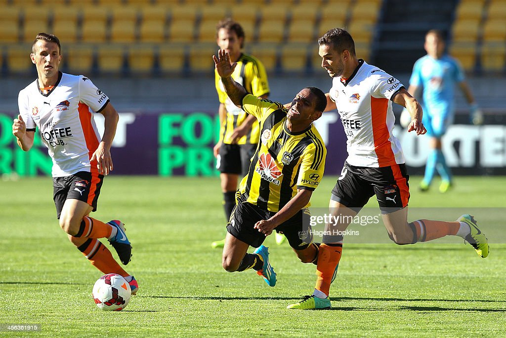 Kenny Cunningham of the Phoenix is brought down in the challenge of Jack Hingert of the Roar during the round 10 A-League match between the Wellington Phoenix and Brisbane Roar at Westpac Stadium on December 14, 2013 in Wellington, New Zealand.