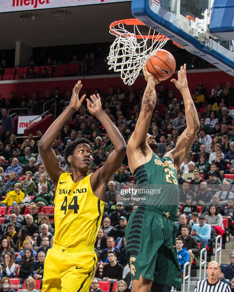 Kenny Goins #25 of the Michigan State Spartans grabs the rebound next to Julius Palmer #44 of the Oakland Golden Grizzlies during game two of the Hitachi College Basketball Showcase at Little Caesars Arena on December 16, 2017 in Detroit, Michigan. The Spartans defeated the Grizzles 86-73.