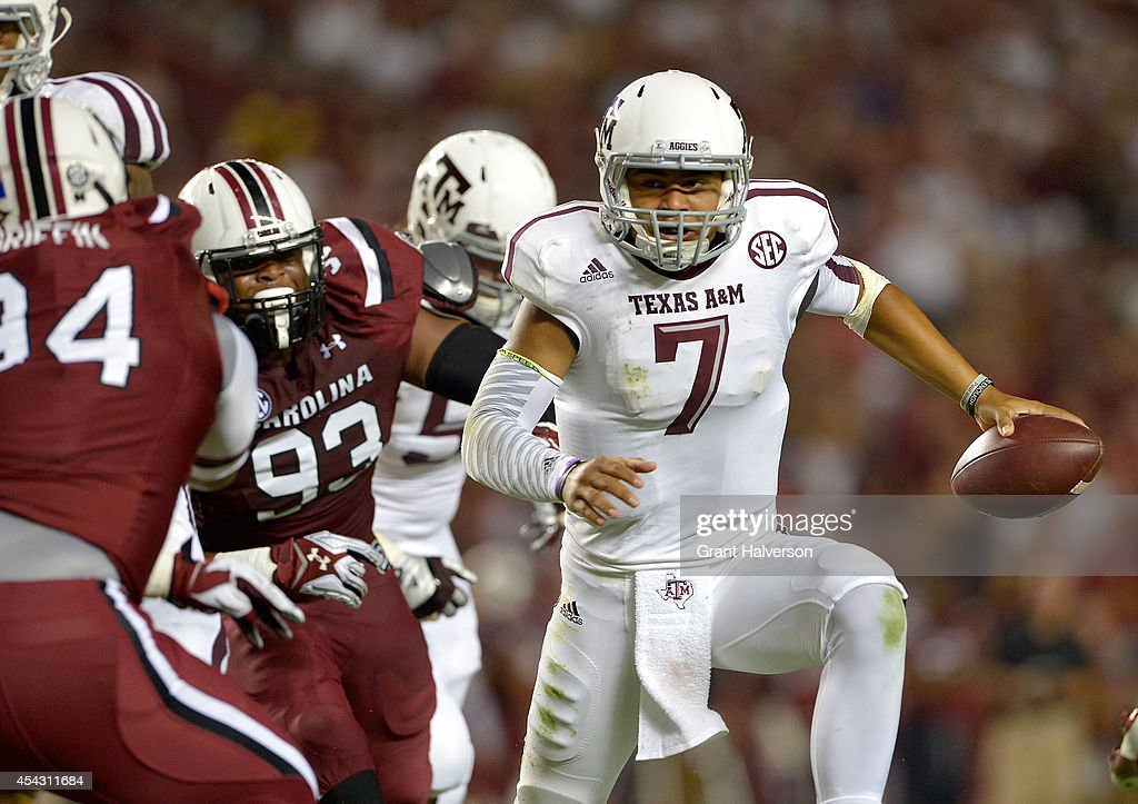 Kenny Hill #7 of the Texas A&M Aggies rols out under pressure from the South Carolina Gamecocks defense during their game at Williams-Brice Stadium on August 28, 2014 in Columbia, South Carolina. Texas A&M won 52-28.