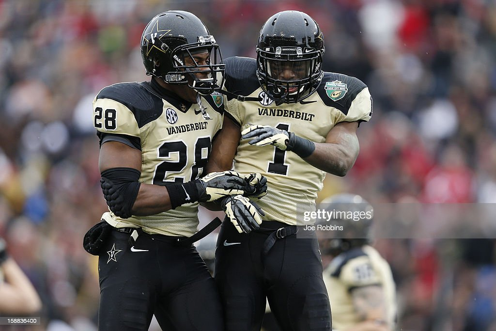 Kenny Ladler #1 and Karl Butler #28 of the Vanderbilt Commodores celebrate after Ladler's interception against the North Carolina State Wolfpack during the Franklin American Mortgage Music City Bowl at LP Field on December 31, 2012 in Nashville, Tennessee.