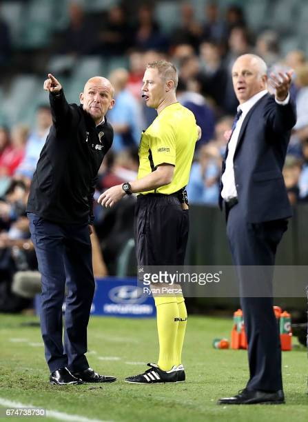 Kenny Lowe manager of the Glory has words with the assistant referee as Graham Arnold coach of of Sydney FC looks on after a video referee decision...