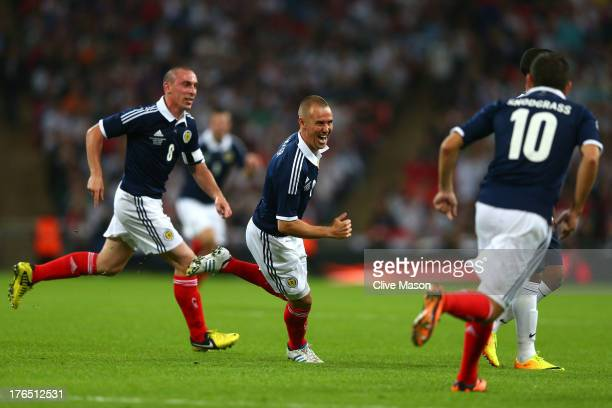 Kenny Miller of Scotland celebrates with teammates Scott Brown of Scotland and Robert Snodgrass of Scotland after scoring a goal during the...
