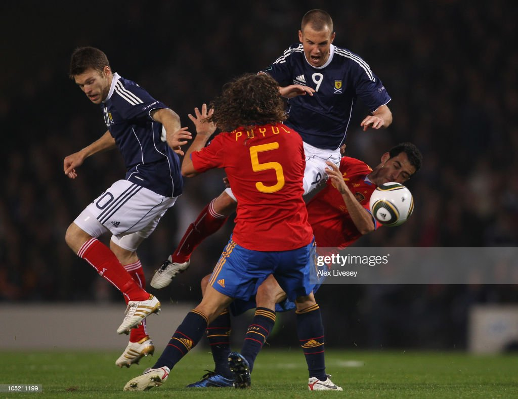 Kenny Miller of Scotland is tackled by Carles Puyol and Sergio Busquets of Spain during the UEFA EURO 2012 Group I Qualifier match between Scotland...