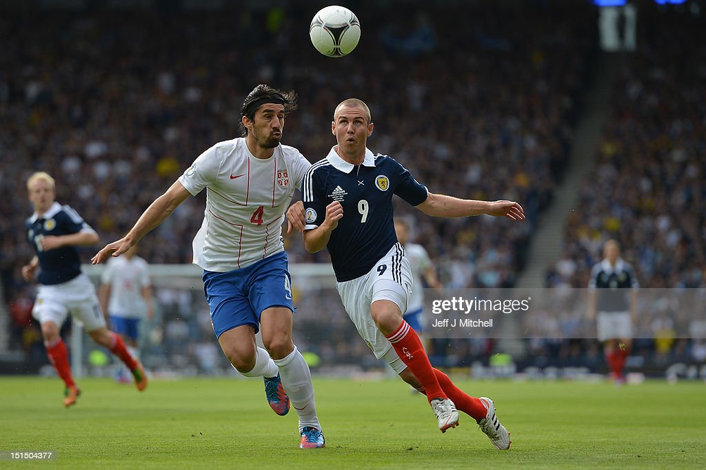<a gi-track='captionPersonalityLinkClicked' href=/galleries/search?phrase=Kenny+Miller&family=editorial&specificpeople=213276 ng-click='$event.stopPropagation()'>Kenny Miller</a> of Scotland tackles <a gi-track='captionPersonalityLinkClicked' href=/galleries/search?phrase=Milan+Bisevac&family=editorial&specificpeople=600075 ng-click='$event.stopPropagation()'>Milan Bisevac</a> of Serbia during the FIFA 2014 World Cup Qualifier at Hampden Park between Scotland and Serbia on September 8, 2012 in Glasgow, Scotland.