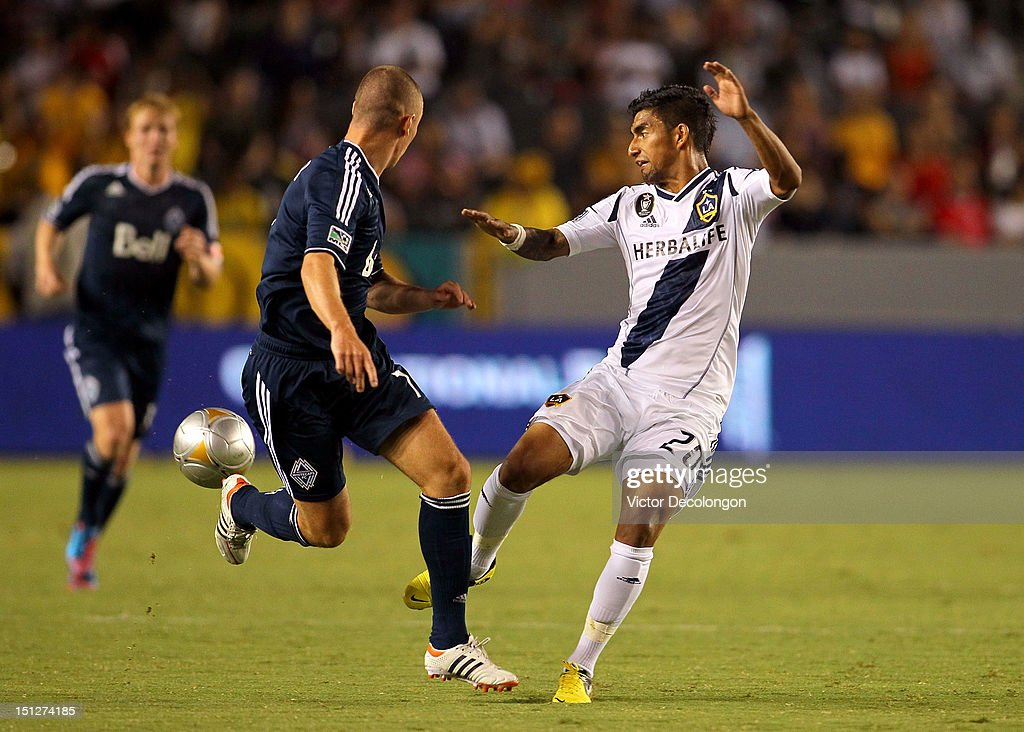 Kenny Miller #7 of the Vancouver Whitecaps and A.J. DeLaGarza #20 of the Los Angeles Galaxy vie for the ball during the MLS match at The Home Depot Center on September 1, 2012 in Carson, California. The Galaxy defeated the Whitecaps 2-0.