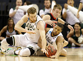 Kenny Paul Geno of the Georgia Bulldogs goes after a loose ball against teammates Matt Costello and Marvin Clark Jr #0 of the Michigan State Spartans...