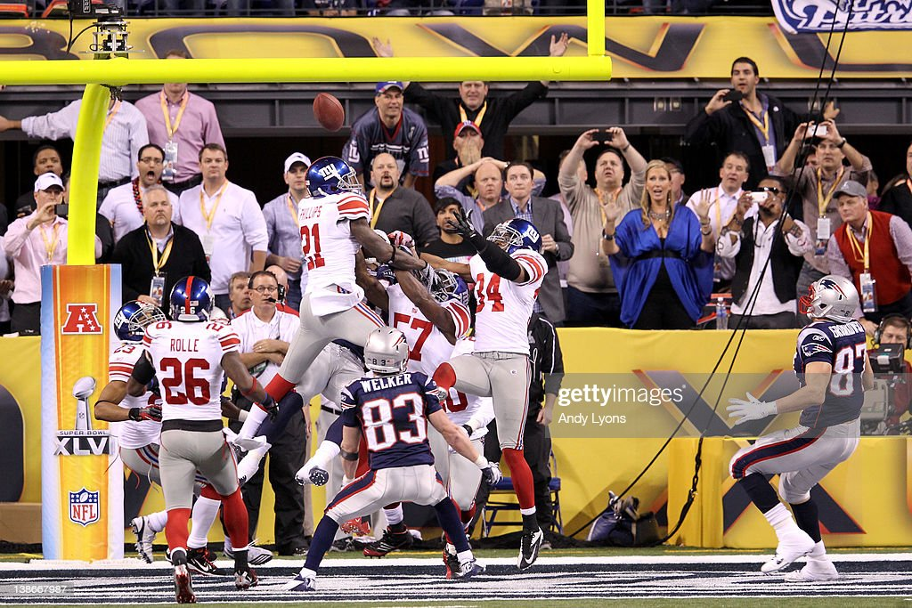 Kenny Phillips #21, Jacquian Williams #57 and Deon Grant #34 of the New York Giants break up a hail mary pass in the final seconds of the fourth quarter against Wes Welker #83 and Rob Gronkowski #87 (R) of the New England Patriots during Super Bowl XLVI at Lucas Oil Stadium on February 5, 2012 in Indianapolis, Indiana.The Giants won 21-17.