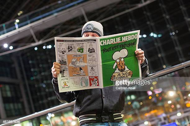Kenny Rebenstock reads an issue of the French satirical magazine Charlie Hebdo the first published after the recent Paris terror attacks in a store...