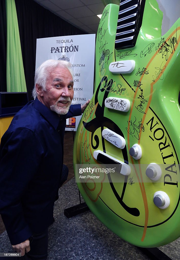 Kenny Rogers signs a giant Patron tequila guitar backstage at the CMA Awards to benefit the 'Keep the Music Playing' music education on November 3, 2013 in Nashville, Tennessee.