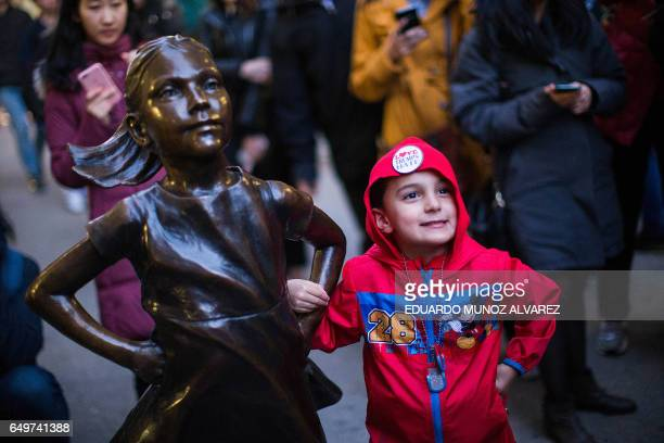 Kenny Simmers from New Jersey poses for a picture next to 'The Fearless Girl' statue as it faces the iconic Wall Street charging bull statue as part...