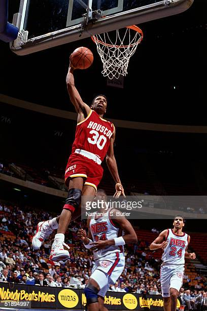 Kenny Smith of the Houston Rockets drives to the basket for a slam dunk against the New Jersey Nets during an NBA game at the Brendan Byrne Arena in...