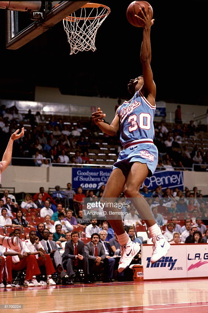 Kenny Smith of the Sacramento Kings drives to the basket for a layup against the Los Angeles Clippers during an NBA game circa 1988 at the LA...