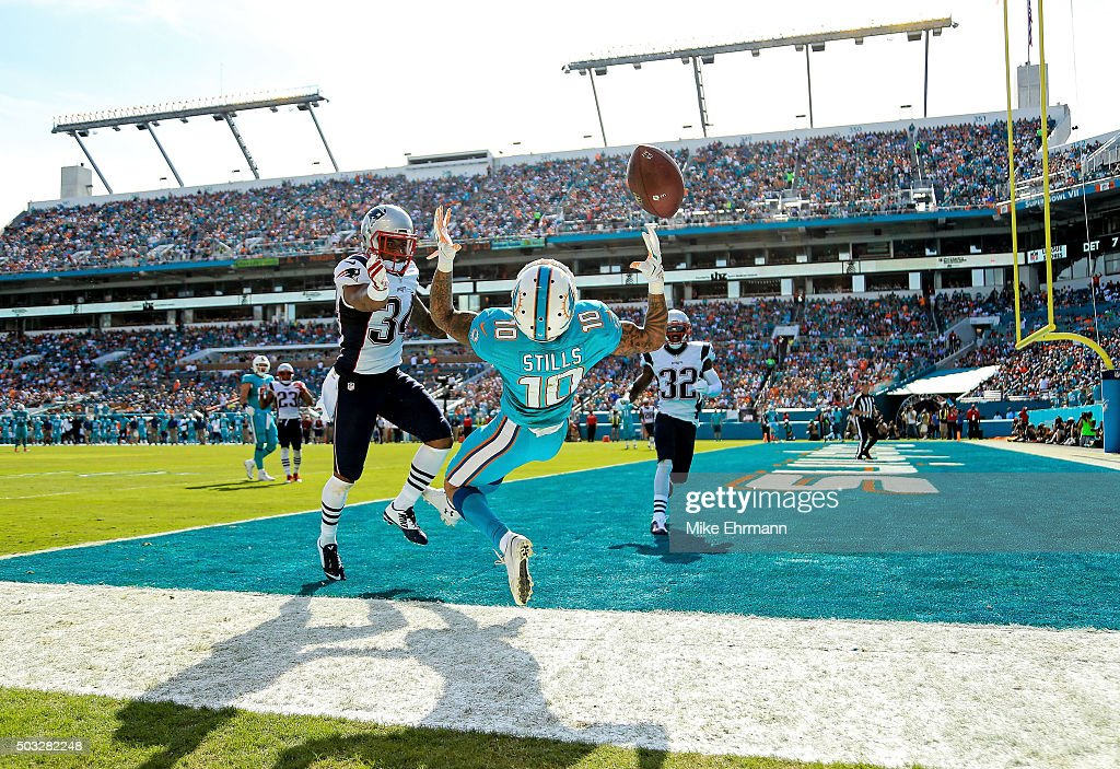 Kenny Stills #10 of the Miami Dolphins attempts to catch a pass while Leonard Johnson #34 of the New England Patriots defends during the first half of the game at Sun Life Stadium on January 3, 2016 in Miami Gardens, Florida.