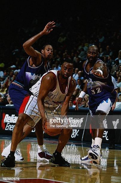 Kenny Thomas of the Houston Rockets moves past Donyell Marshall and Karl Malone of the Utah Jazz during the game on March 27 2001 at the Compaq...