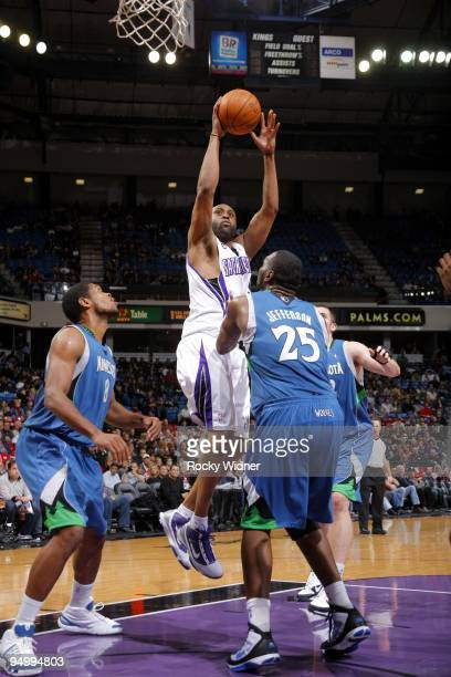 Kenny Thomas of the Sacramento Kings goes up for a shot against Al Jefferson and Ryan Gomes of the Minnesota Timberwolves during the game at Arco...