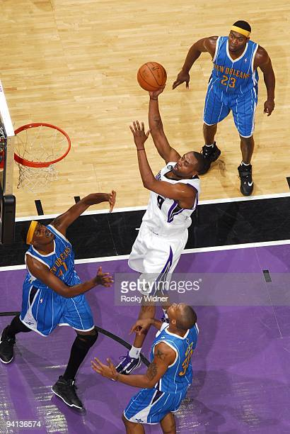 Kenny Thomas of the Sacramento Kings goes up for a shot against James Posey and David West of the New Orleans Hornets during the game at Arco Arena...