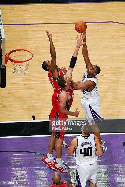 Kenny Thomas of the Sacramento Kings hooks a shot over Sean Williams and Brook Lopez of the New Jersey Nets during the game on November 27 2009 at...