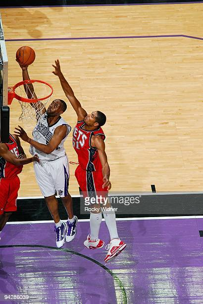 Kenny Thomas of the Sacramento Kings lays up a shot against Sean Williams of the New Jersey Nets during the game on November 27 2009 at Arco Arena in...