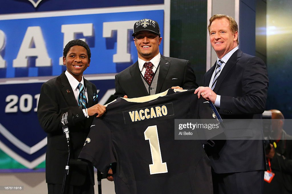 Kenny Vaccaro of the Texas Longhorns, stands with 13-year-old Markell Gregoire (L) and NFL Commissioner Roger Goodell (R) as they hold up a jersey on stage after he was picked #15 overall by the New Orleans Saints in the first round of the 2013 NFL Draft at Radio City Music Hall on April 25, 2013 in New York City.