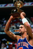 Kenny Walker of the New York Knicks raises the trophy for the Gatorade SlamDunk Competition during the 1989 NBA AllStar Weekend at the Houston...