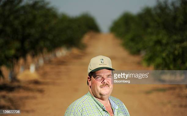 Kenny Watkins stands for a portrait among walnut trees on his farm in Linden California US on Wednesday Sept 14 2011 Watkins a fifthgeneration farmer...