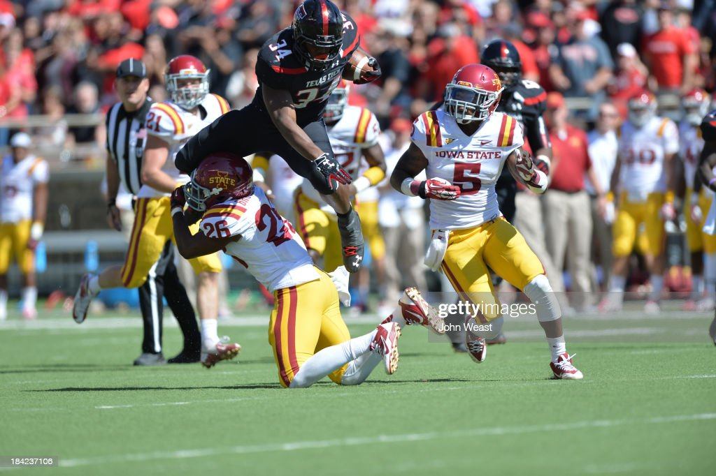 Kenny Williams #34 of the Texas Tech Red Raiders gets upended by Deon Broomfield #26 of the Iowa State Cyclones during game action on October 12, 2013 at AT&T Jones Stadium in Lubbock, Texas. Texas Tech won the game over Iowa State 42-35.