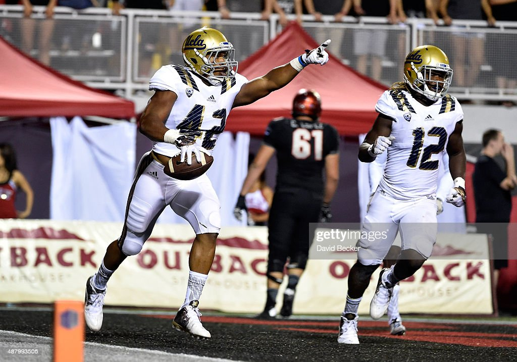 Kenny Young #42 celebrates a touchdown with teammate Jayon Brown #12 both of the UCLA Bruins after intercepting a pass from the UNLV Rebels during a game at Sam Boyd Stadium on September 12, 2015 in Las Vegas, Nevada.