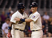 Kennys Vargas and Joe Mauer of the Minnesota Twins celebrate a walkoff win of the game against the Cleveland Indians in the early morning hours on...