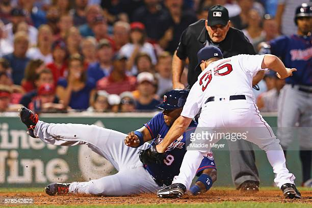 Kennys Vargas of the Minnesota Twins slides safely into home past Steven Wright of the Boston Red Sox during the fifth inning at Fenway Park on July...
