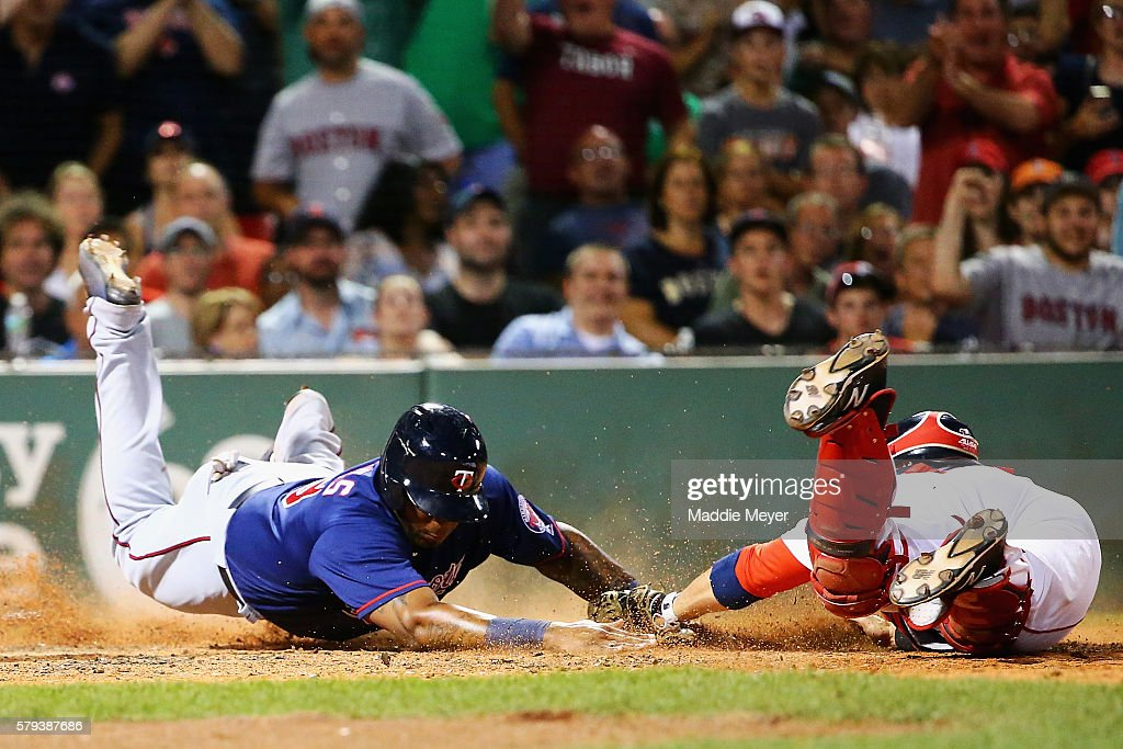 Kennys Vargas #19 of the Minnesota Twins slides safely into home past Sandy Leon #3 of the Boston Red Sox during the seventh inning at Fenway Park on July 23, 2016 in Boston, Massachusetts.