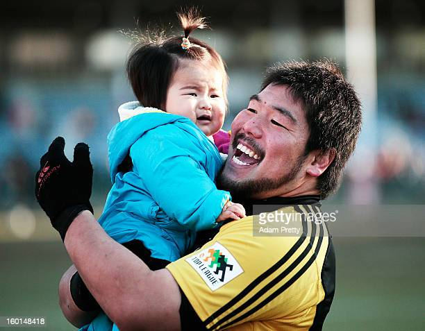 Kensuke Hatakeyama of Suntory celebrates with his baby after victory in the Japan Rugby Top League playoff final match between Suntory Sungoliath and...