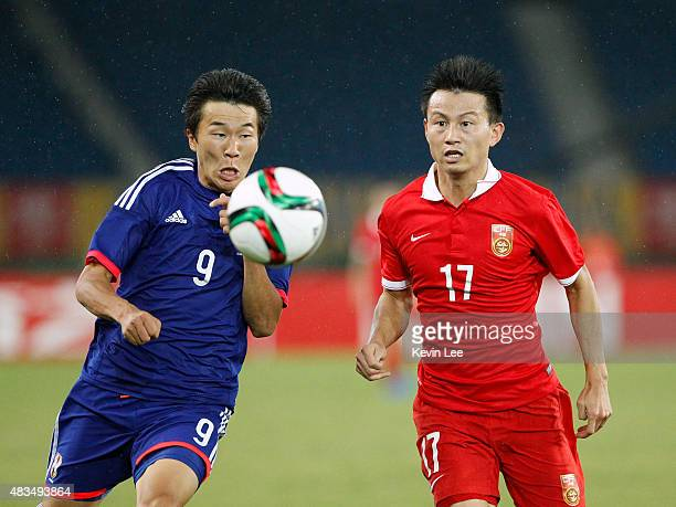 Kensuke Nagai of Japan battles for the ball against Rao Weihui of China during the EAFF East Asian Cup 2015 final round at the Wuhan Sports Center...