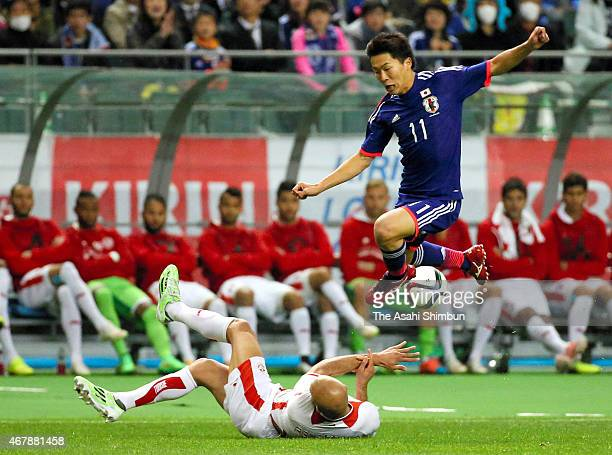 Kensuke Nagai of Japan is tackled by Aymen Abdennour of Tunisia during the international friendly match between Japan and Tunisia at Oita Bank Dome...