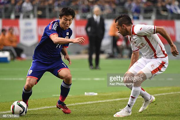 Kensuke Nagai of Japan keeps the ball under the pressure from Syam Ben Youssef of Tunisia during the international friendly match between Japan and...