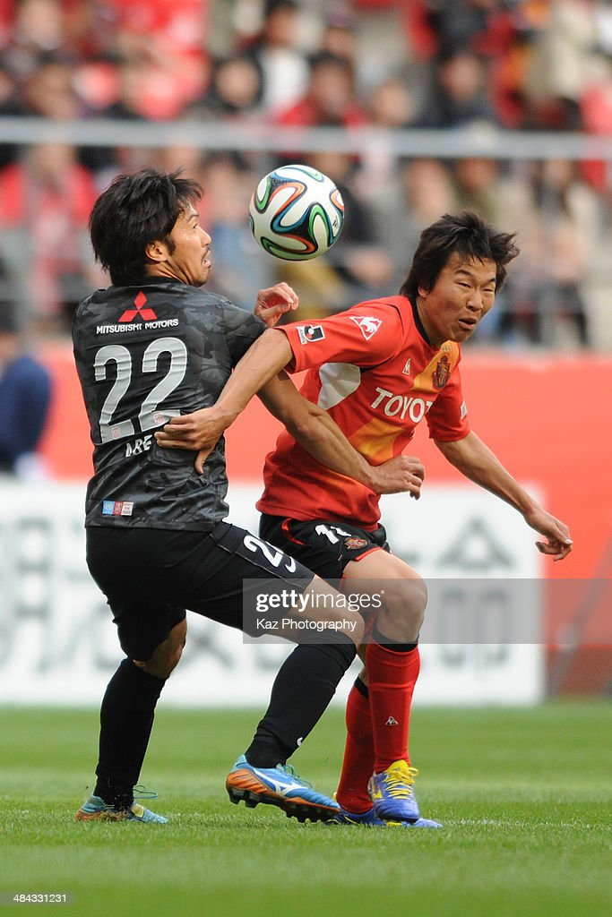 Kensuke Nagai (R) of Nagoya Grampus and Yuki Abe of Urawa Red Diamonds compete for the ball during the J. League match between Nagoya Grampus and Urawa Red Diamonds at the Toyota Stadium on April 12, 2014 in Toyota, Japan.