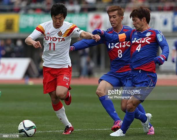 Kensuke Nagai of Nagoya Grampus competes for the ball against Hideomi Yamamoto and Ryohei Arai of Ventforet Kofu during the JLeague match between...
