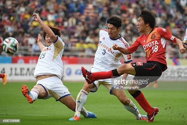 Kensuke Nagai of Nagoya Grampus shoots the ball under the pressure from Masato Morishige and Kazunori Yoshimoto of FC Tokyo during the JLeague match...