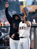 Kensuke Tanaka and Tony Abreu of the San Francisco Giants wave to a fan in the dugout before his Major League Baseball debut game against the New...