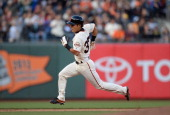 Kensuke Tanaka of the San Francisco Giants goes from first to third on a double by Andres Torres in the ninth inning against the Cincinnati Reds at...