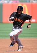 Kensuke Tanaka of the San Francisco Giants runs safely to third base during the game against the Texas Rangers at Surprise Stadium on March 11 2013...