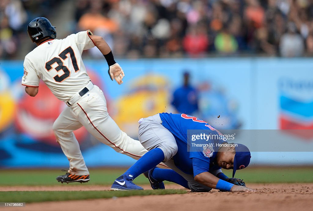 Kensuke Tanaka #37 of the San Francisco Giants steals second base as the ball is thrown into centerfield past Starlin Castro #13 of the Chicago Cubs in the ninth inning at AT&T Park on July 28, 2013 in San Francisco, California. Tanaka went to third on the throwing error.
