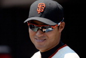 Kensuke Tanaka of the San Francisco Giants wearing Oakley Sunglasses looks on from the dugout before the start of his game against the Arizona...