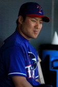 Kensuke Tanaka of the Texas Rangers watches action on the field during a spring training baseball game against the the Cleveland Indians on March 3...