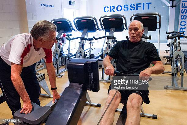 Kent and Sussex Crossfit gym Man 7080years old on rowing machine Advice and encouragement from friend and written on the wall behind